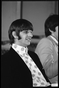 Thumbnail of Ringo Starr seated at a table during a Beatles press conference