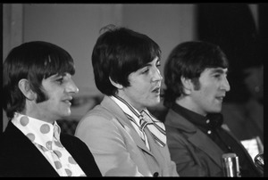 Thumbnail of Ringo Starr, Paul McCartney, and John Lennon (l. to r.) seated at a table during a Beatles press conference