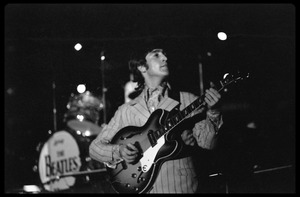 Thumbnail of John Lennon (the Beatles) playing guitar in concert at D.C.             Stadium