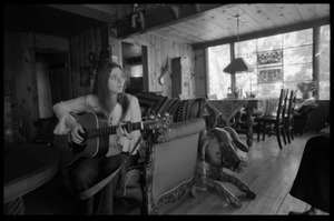 Thumbnail of Judy Collins: playing guitar while seated on a couch in Joni Mitchell's house in         Laurel Canyon
