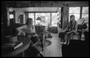 Thumbnail of Judy Collins with guitar and Joni Mitchell, in Mitchell's house in Laurel Canyon
