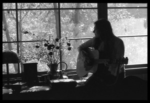 Thumbnail of Judy Collins playing guitar while silhouetted against a window in Joni Mitchell's house in Laurel Canyon