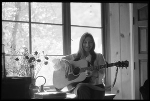 Thumbnail of Judy Collins seated in a window at Joni Mitchell's house in Laurel Canyon,             playing guitar