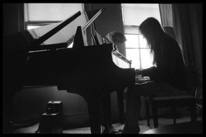 Thumbnail of Judy Collins silhouetted against a window, playing piano in her New York             apartment