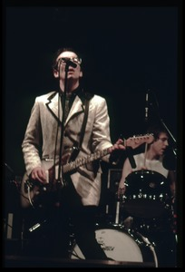 Thumbnail of Elvis Costello and the Attractions in concert: Costello on guitar and vocals         (drummer Bruce Thomas in background)