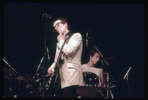 Thumbnail of Elvis Costello and the Attractions in concert: Costello on guitar, drummer             Bruce Thomas in background