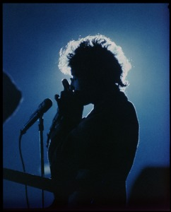 Thumbnail of Bob Dylan, silhouetted in blue Dylan in concert at the Washington Coliseum, playing harmonica
