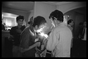 Thumbnail of Unidentified man at a reception lighting a cigarette for Bob Dylan, Newport Folk Festival