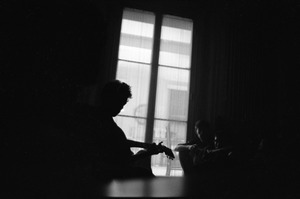 Thumbnail of Bob Dylan silhouetted against a window, playing a guitar backstage, Newport Folk Festival