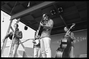 Thumbnail of The  Dillards performing on stage, Newport Folk Festival Left to right: Dean Webb, Doug Dillard (obscured), Rodney Dillard, Mitchell Jayne