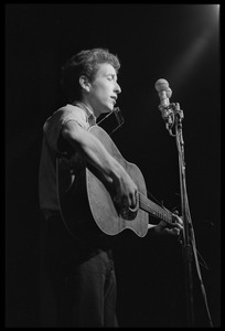 Thumbnail of Bob Dylan, with guitar and harmonica, performing on stage, Newport Folk Festival