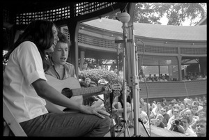 Thumbnail of Bob Dylan and Joan Baez performing on Porch #1, Newport Folk Festival View from stage right, with stands in the background