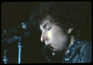 Thumbnail of Bob Dylan performing on stage, playing harmonica Dylan in concert at the Washington Coliseum