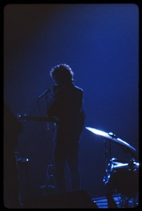 Thumbnail of Bob Dylan performing on stage, silhouetted in blue Dylan in concert at the Washington Coliseum
