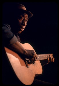 Thumbnail of Mississippi John Hurt: studio portrait, seated, playing guitar
