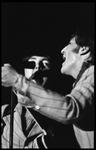 Thumbnail of John Lennon and Paul McCartney (partially obscured) performing with the Beatles at D.C. Stadium