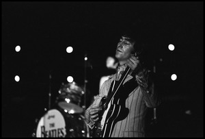 Thumbnail of John Lennon performing with the Beatles at D.C. Stadium Half-length portrait with Ringo's drum kit in the background
