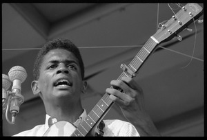 Thumbnail of Jackie Washington on stage, playing guitar, Newport Folk Festival