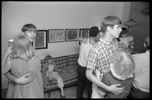 Thumbnail of Teenage long hair: boys and girls slow-dancing at a teenage dance party, as a             young boy watches from the couch