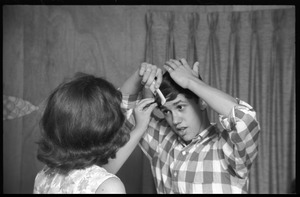 Thumbnail of Teenage long hair: boy combing his shaggy hair as a girl looks on