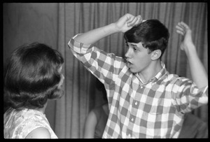 Thumbnail of Teenage long hair: boy combing his hair as a girl looks on