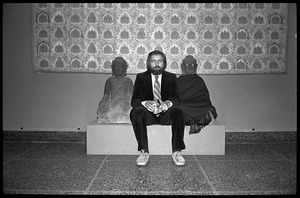 Thumbnail of Rowland Scherman seated between Buddha sculptures while taking a break at the             Birmingham Museum of Art