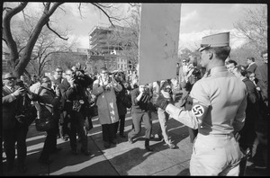Thumbnail of American Nazi Party counter-protester Douglas L. Niles (back to             camera), in uniform, carrying a sign, and facing news media: Washington Vietnam March for Peace