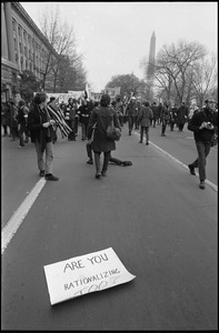 Thumbnail of Anti-Vietnam War marchers in the streets of Washington during the             Counter-inaugural demonstrations, 1969 Sign fallen in the street read 'Are you rationalizing too?'