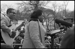 Thumbnail of Fannie Lou Hamer singing at the microphones, accompanied by a guitarist, during a             civil rights demonstration, in front of the White House on Lafayette Square