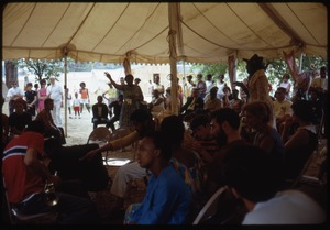 Thumbnail of Group gathering to hear speakers under a large tent at the Resurrection City encampment