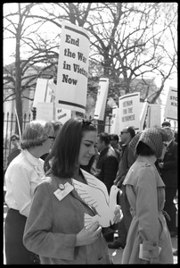 Thumbnail of Woman holding a cutout cardboard peace dove and antiwar demonstrators standing in front of the White House during             the March on Washington