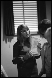 Thumbnail of Young woman distributing tests at the Selective Service College Qualification             examination to determine eligibility for an educational deferment from service in the             Vietnam War