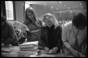 Thumbnail of Young women distributing tests at the Selective Service College Qualification             examination to determine eligibility for an educational deferment from service in the             Vietnam War