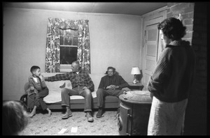 Thumbnail of Richard Loving (center) seated on a couch, flanked by his son Donald (?) and             father, Mildred Loving standing by the wall