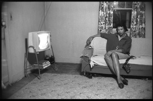 Thumbnail of Mildred Loving, seated on couch, the television on