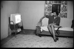 Thumbnail of Mildred Loving, seated on couch, watching television