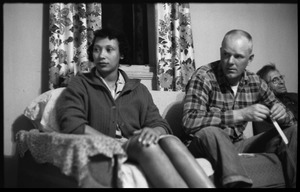 Thumbnail of Mildred and Richard Loving seated on a couch with Richard's father (from left)