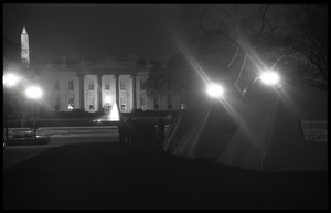 Thumbnail of Nighttime view of the tents, one with a sign reading 'Houses not tents,' the             White House and Washington Monument in the background Strike City Mississippi tent encampment