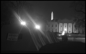 Thumbnail of Nighttime view of a row of tents, one with a sign reading 'Houses not tents,' the             White House and Washington Monument in the background Strike City Mississippi tent encampment