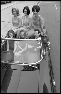 Thumbnail of Michael O'Harro (at wheel) with five women packed into his convertible Corvette Stingray             sports car