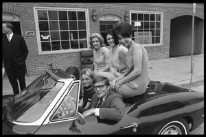 Thumbnail of JOPA staff member with five women packed into a convertible Corvette Stingray             sports car, stopped in front of the JOPA headquarters on M Street NW