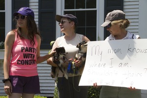 Thumbnail of Pro-immigration protesters and their dogs outside the Chatham town offices             building with sign reading 'My mom knows where I am, shouldn't theirs?' : taken at the 'Families Belong Together' protest against the Trump             administration's immigration policies