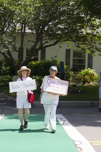 Thumbnail of Two women pro-immigration protesters in a cross-walk over Main Street carrying signs reading             'Hate separates' and 'Our choices define us' : taken at the 'Families Belong Together' protest against the Trump             administration's immigration policies