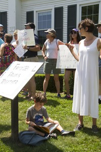 Thumbnail of Pro-immigration rally in front of the Chatham town offices building, with             young boy seated on the grass, reading a book : taken at the 'Families Belong Together' protest against the Trump             administration's immigration policies