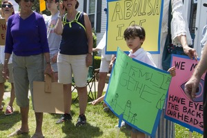 Thumbnail of Young boy carrying a sign reading 'Keep families together' at a pro-immigration             rally in front of the Chatham town offices building : taken at the 'Families Belong Together' protest against the Trump administration's immigration policies