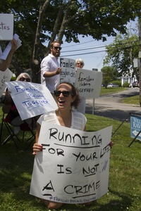 Thumbnail of Pro-immigration protesters in front of the Chatham town offices building, one             seated on the grass with a sign reading 'Running for your life is not a crime' : taken at the 'Families Belong Together' protest against the Trump administration's immigration policies