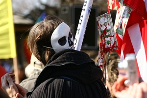 Thumbnail of Protesters carrying an American flag hung with bloody dollar bills and wearing a             skull mask: rally and march against the Iraq War