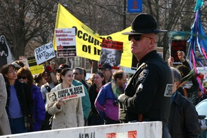 Thumbnail of Police officer looking away from protesters holding signs: 'George W. Bush: like             a rock, only dumber' and 'Drop acid, not bombs': rally and march against the Iraq War