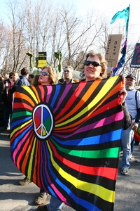 Thumbnail of Women holding a banner with rainbow hues and a peace symbol: rally and march against the Iraq War