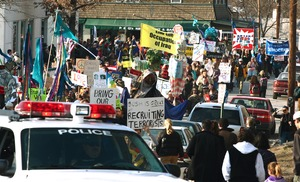 Thumbnail of Police car leading anti-war marchers through the streets, led by banner reading             'Bring the troops home now': rally and march against the Iraq War